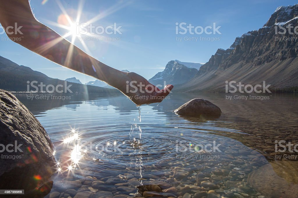 Human hand cupped to catch the fresh water from the lake, sunlight...
