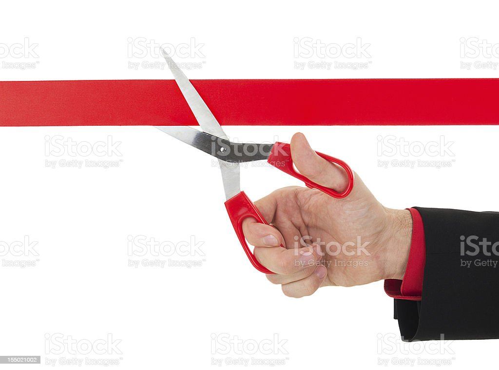 human hand cutting the red ribbon with scissors stock photo