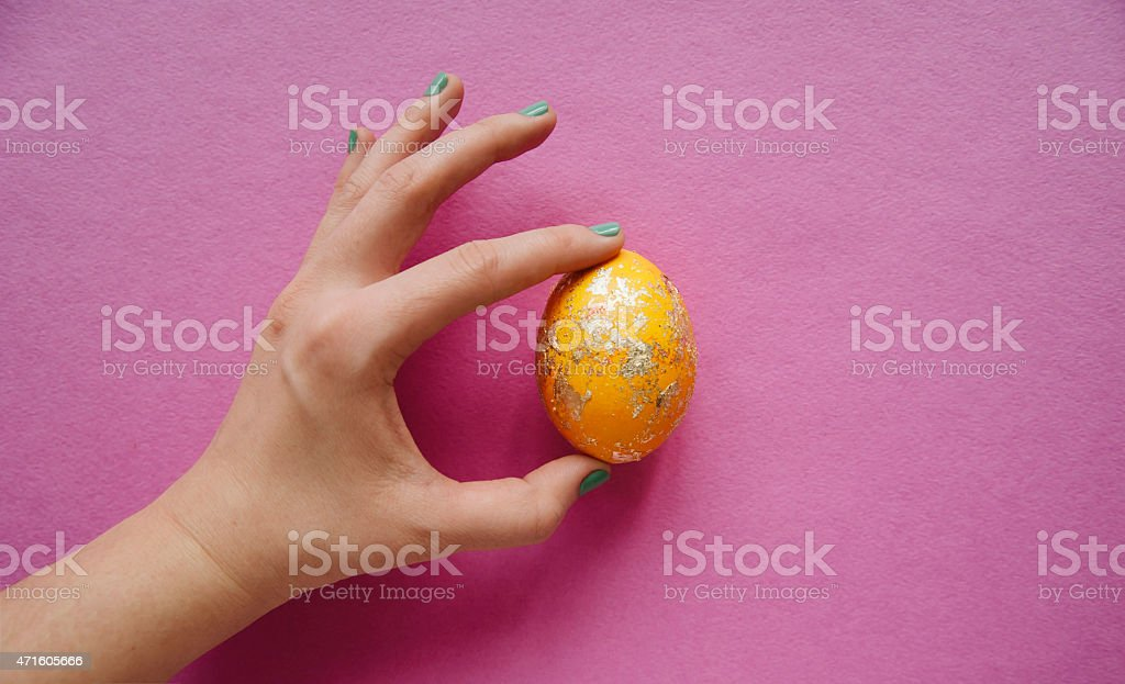 human hand holding a foiled yellow easter egg stock photo