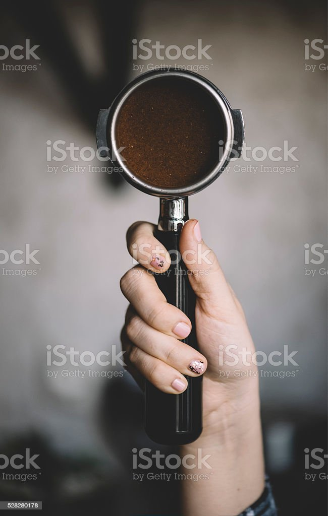 Human hand holding a portafilter with freshly ground morning coffee stock photo