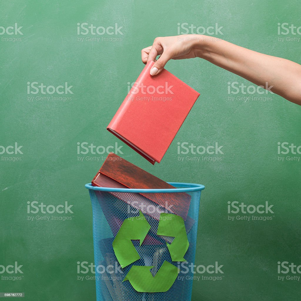 Human Hand Holding A Red Book Over Recycling Bin stock photo