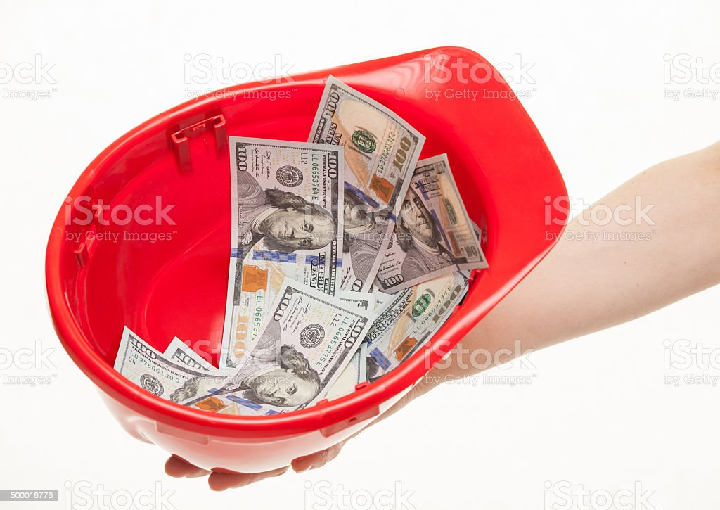 Human hand holding a red hard hat with money stock photo