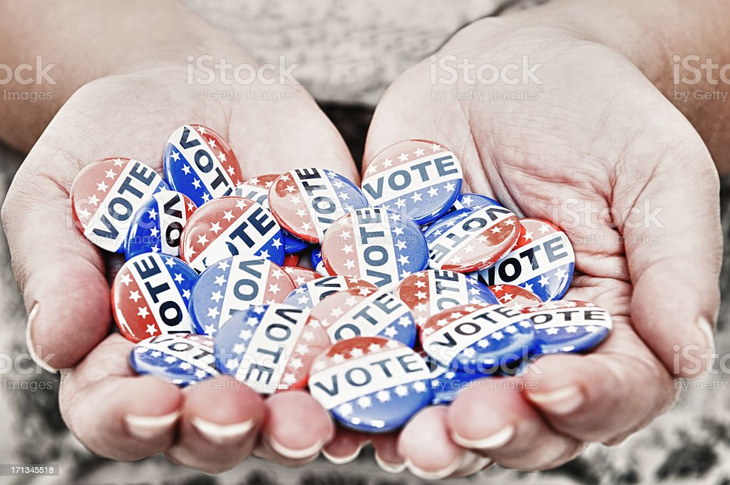 Human hand holding a Vote badge stock photo
