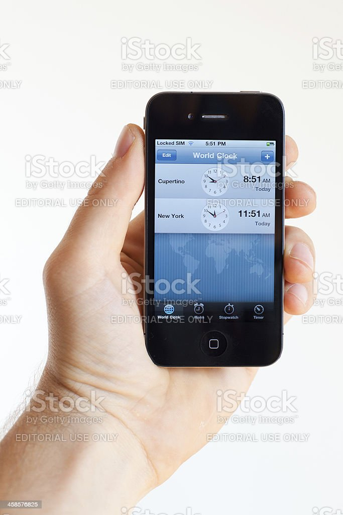 Human hand holding an iphone 4 with world clock application stock caucasian ethnicity computer monitor human hand log on map human hand holding an iphone 4 with world clock gumiabroncs Images