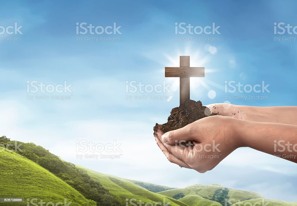 Human hand holding christian cross with soil on the hand stock photo