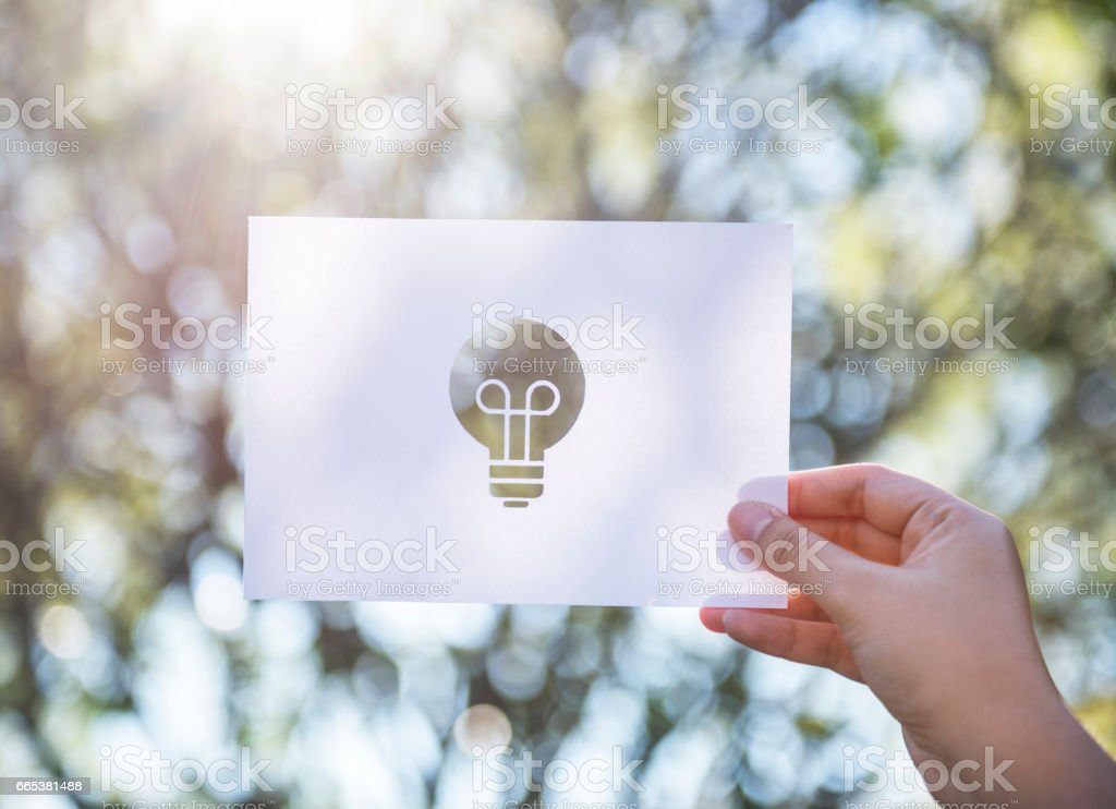 Human hand holding light bulb perforated paper craft in nature stock photo