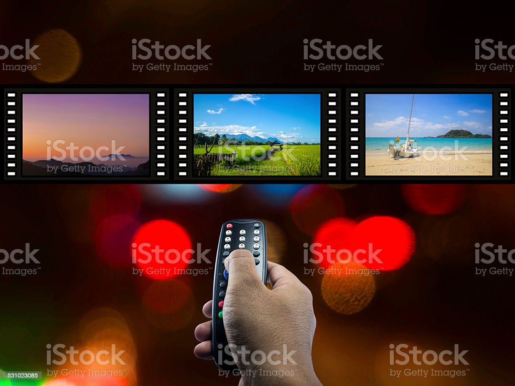 Human hand holding remote and l tree flim stock photo