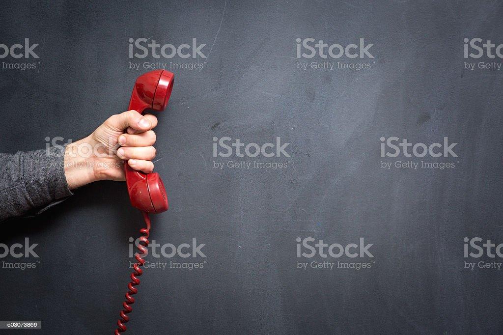Human hand holding telephone on blackboard - Contact Us stock photo