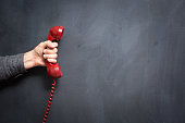 Human hand holding telephone on blackboard - Contact Us