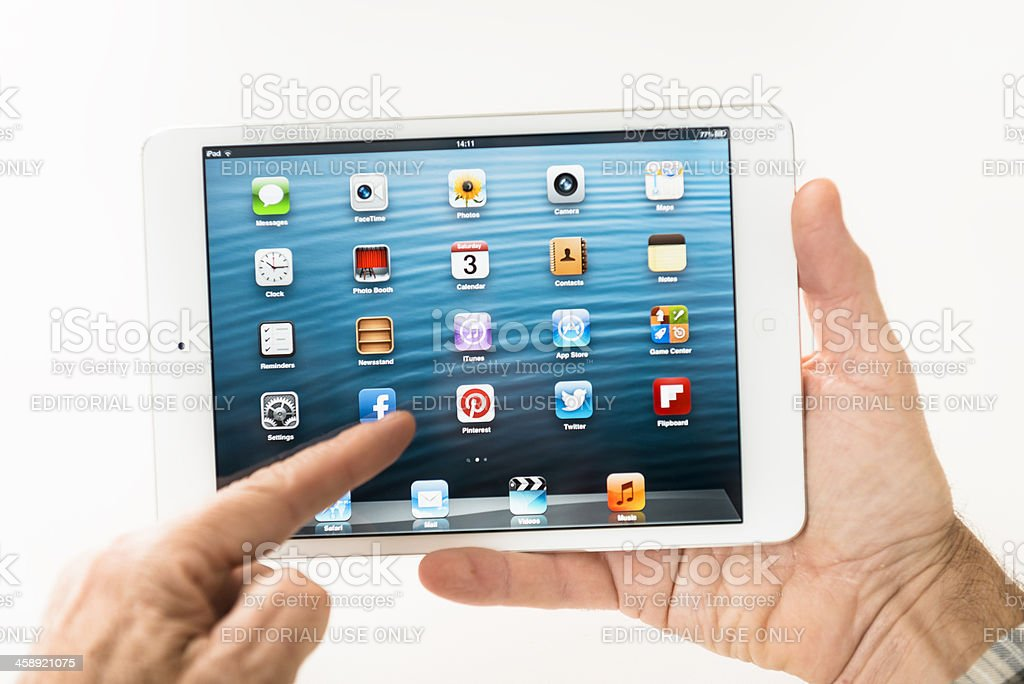 Human hand holding the new Ipad Mini and scrolling stock photo