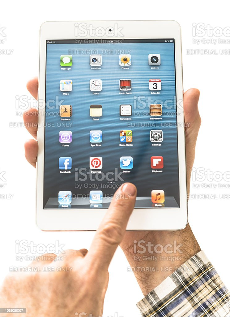 Human hand holding the new Ipad Mini and scrolling royalty-free stock photo