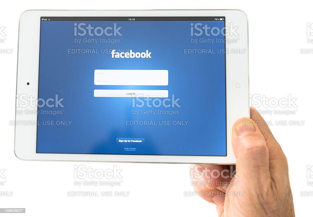 Human hand holding the new Ipad Mini with facebook.com app stock photo