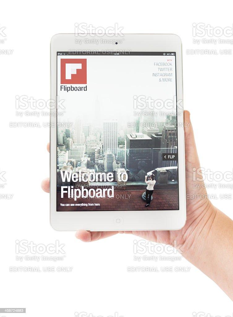 Human hand holding the new Ipad Mini with flipboard app stock photo