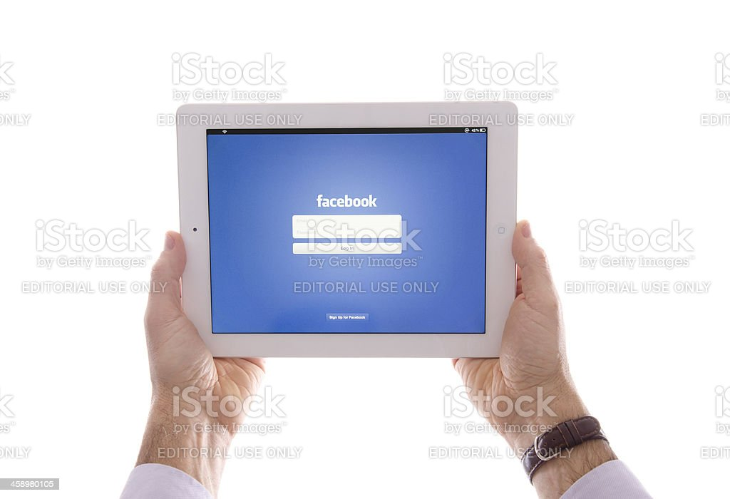 Human hand holding the new Ipad with Facebook app stock photo