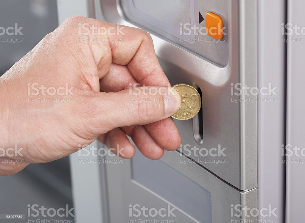 Human hand inserting coin in vending machine stock photo
