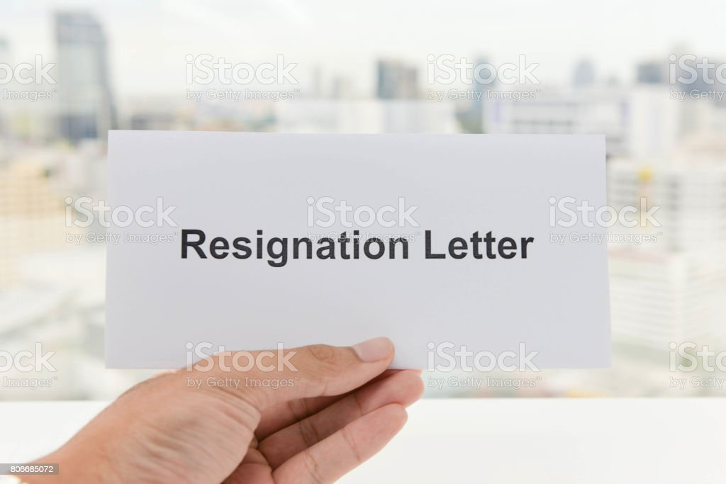 Human hand is holding the Resignation letter stock photo