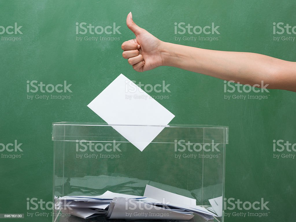 Human hand making thumb up on transparent ballot box stock photo