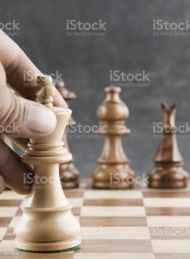 Human hand moving a king chess piece stock photo