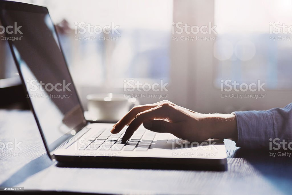 Human hand on laptop keyboard stock photo