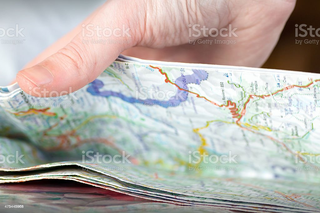 Human hand opening folded colorful map selective focus stock photo