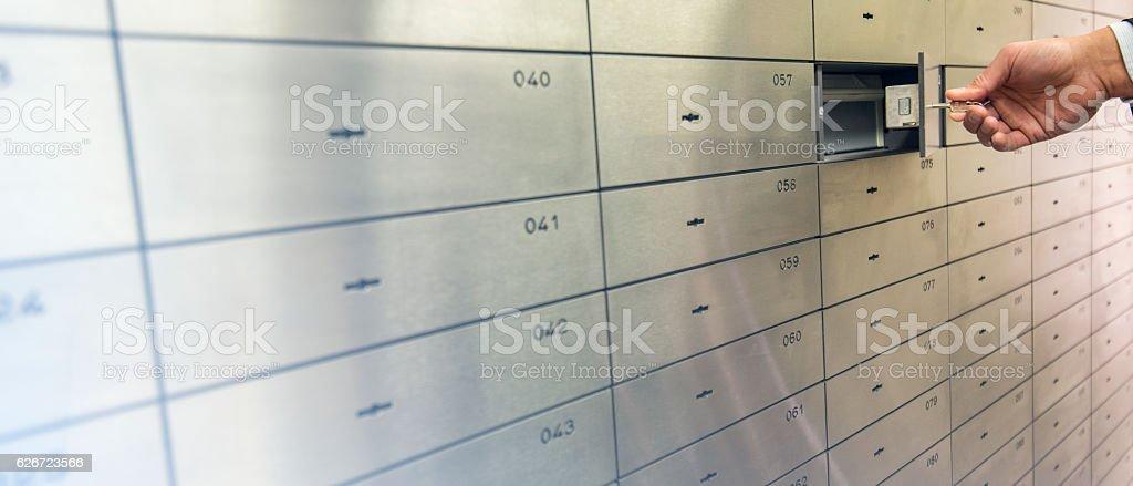 Human hand opening safety deposit box stock photo