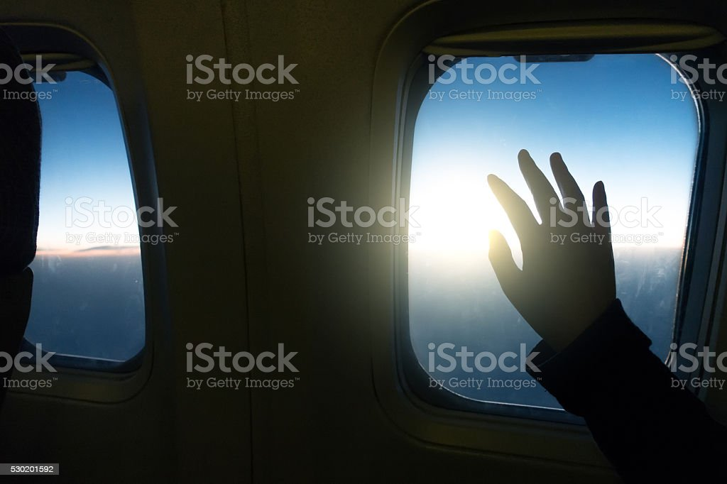 Human hand over airplane window stock photo