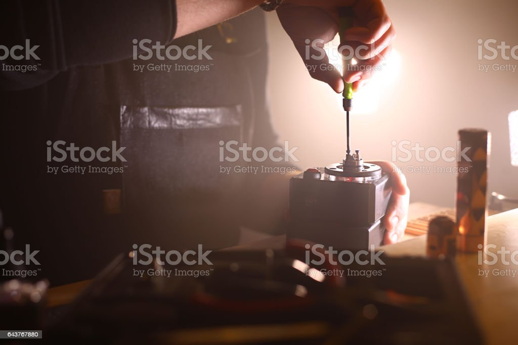 Human hand performing maintenance an electronic cigarette stock photo