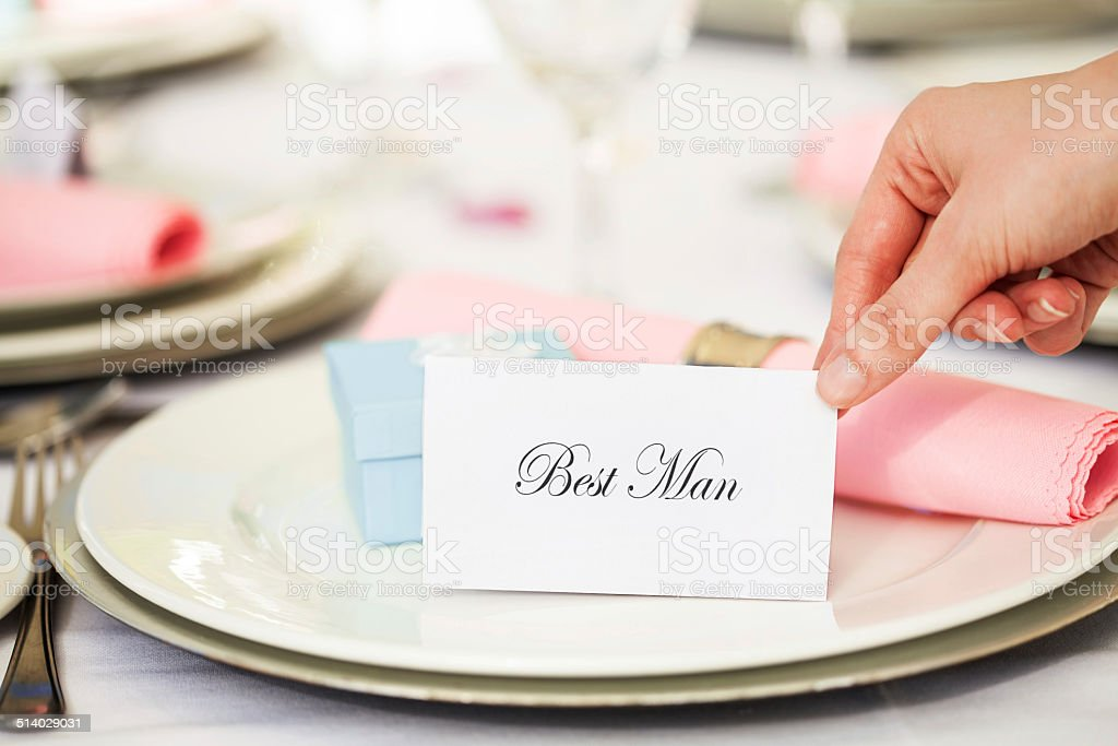 Human Hand Placing 'Best Man' Place Card On Plate stock photo