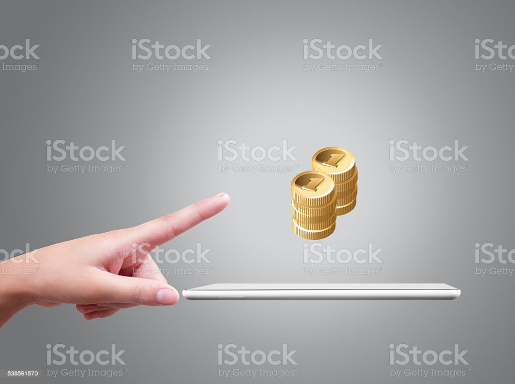Human hand pointing towards gold coins above digital tablet stock photo