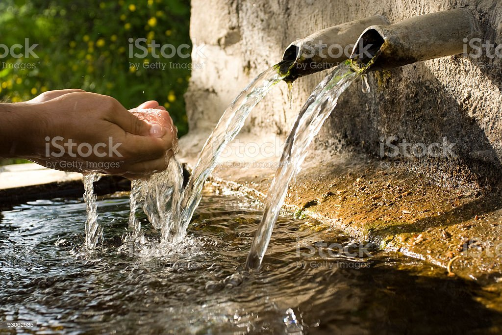 Human hand reaching for water spilling out of stone fountain stock photo