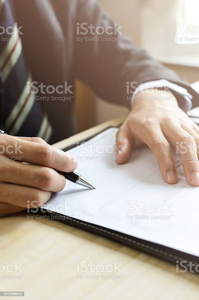 Human Hand Signing on Formal Paper at the workplace stock photo