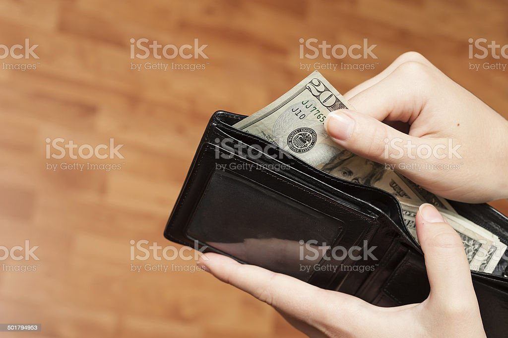 Human hand takes money bills from wallet closeup stock photo