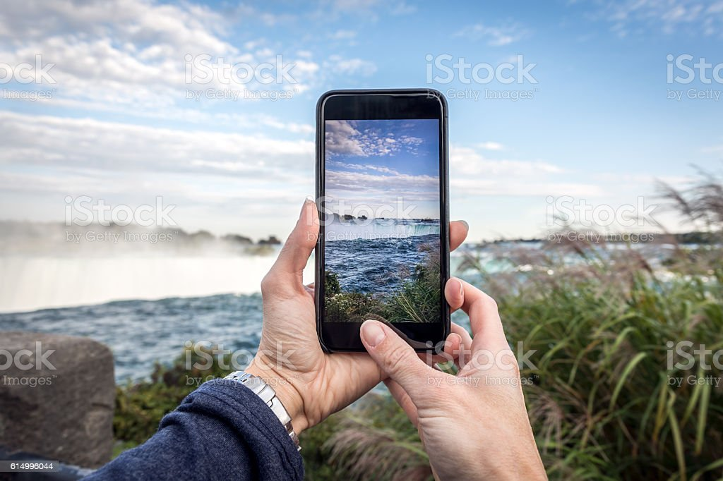 Human Hand Taking Picture at Niagara Falls with Smart phone stock photo