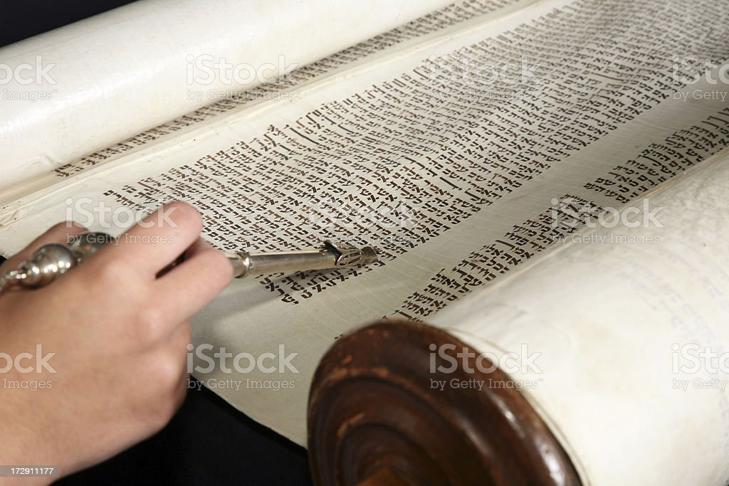 Human hand with a yad touching the torah. stock photo