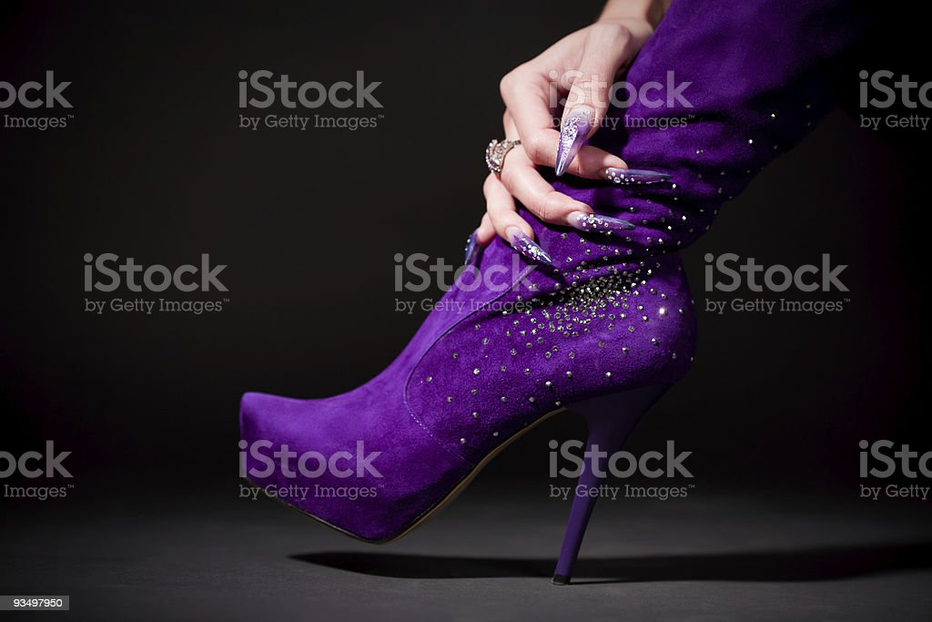 Human hand with beautiful manicure hold purple boot royalty-free stock photo