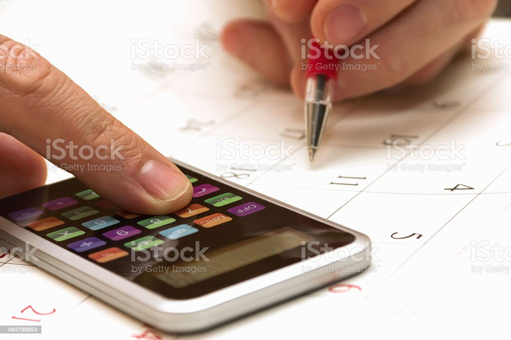 human hand with calculator and pen stock photo