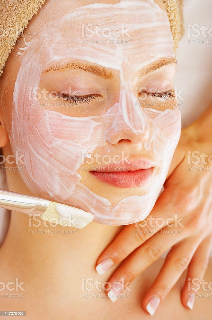 Human hands applying facial mask on a young woman royalty-free stock photo