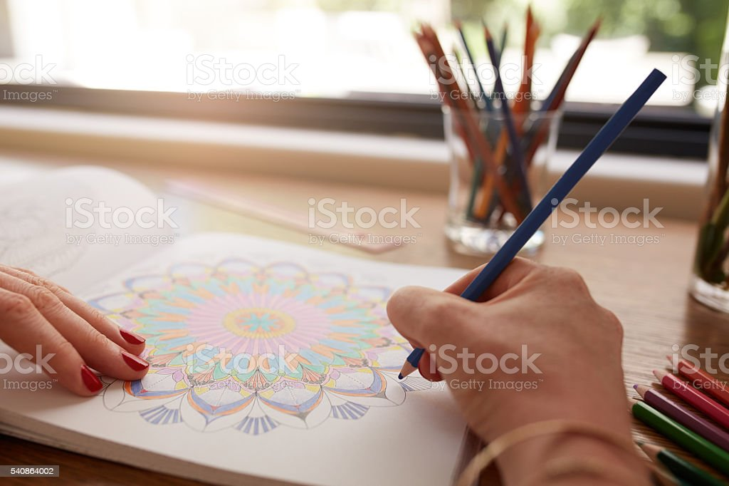 Human hands drawing in adult coloring book stock photo