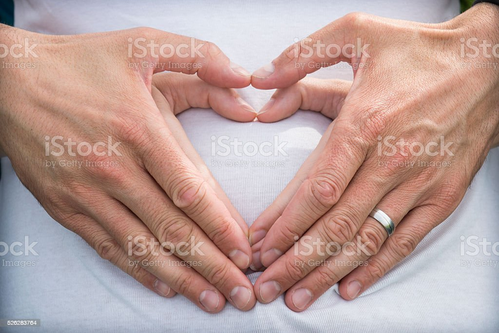 4 human hands forming a heart on belly stock photo