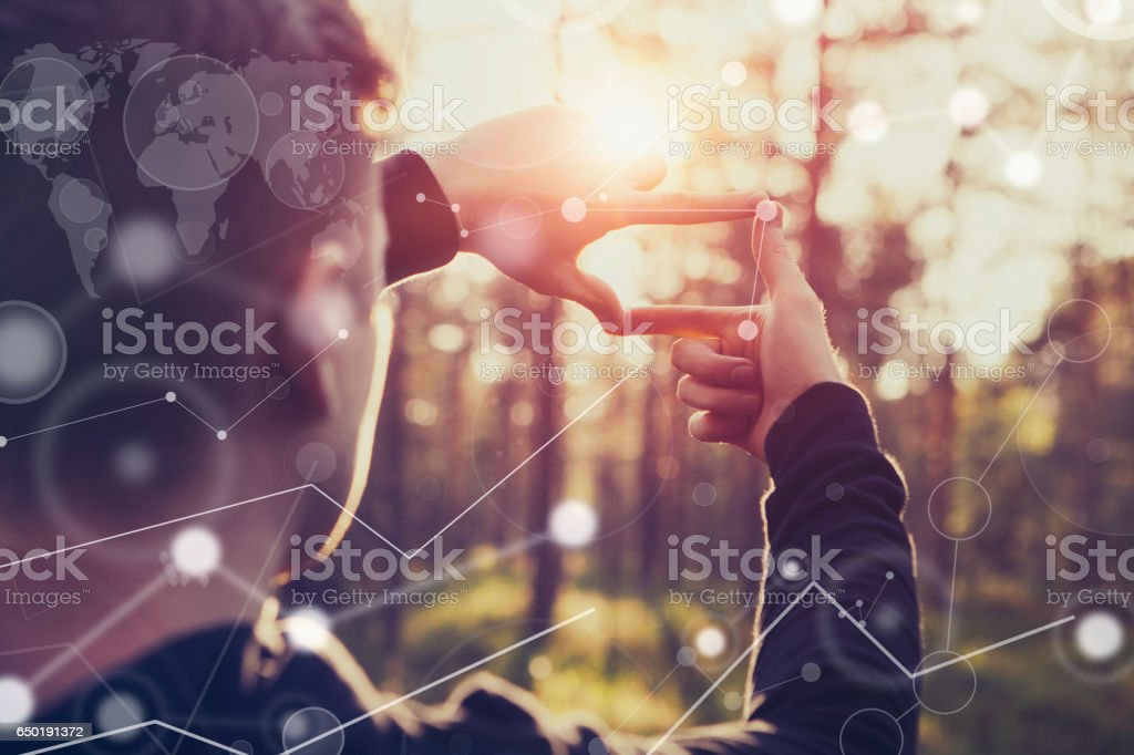 Human hands framing distant sun rays stock photo