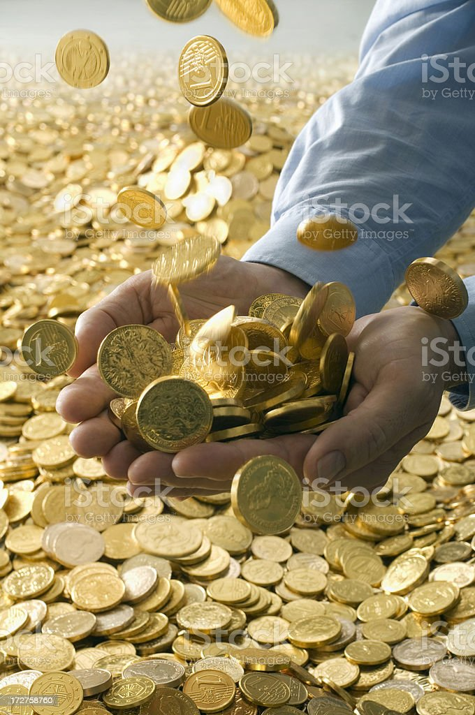 Human hands full of gold coins stock photo