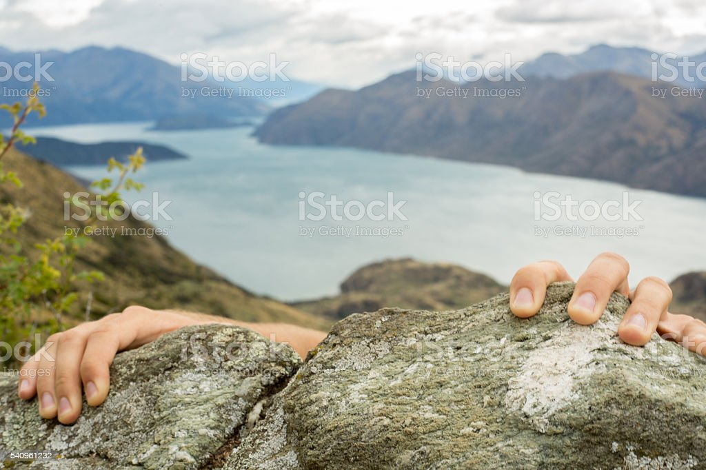 Human hands grabbing last rock at top of mountain peak stock photo