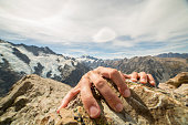 Human hands grabbing last rock at top of mountain peak
