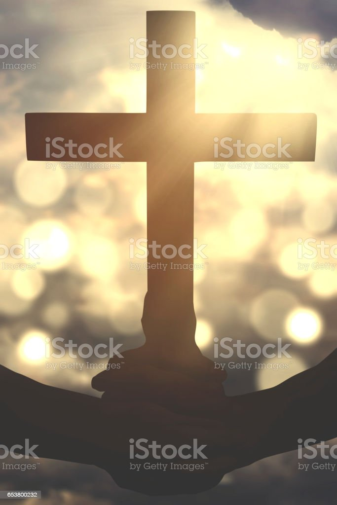 Human hands hold a crucifix symbol stock photo