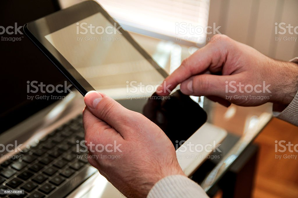 Human hands holding a tablet and using at home stock photo