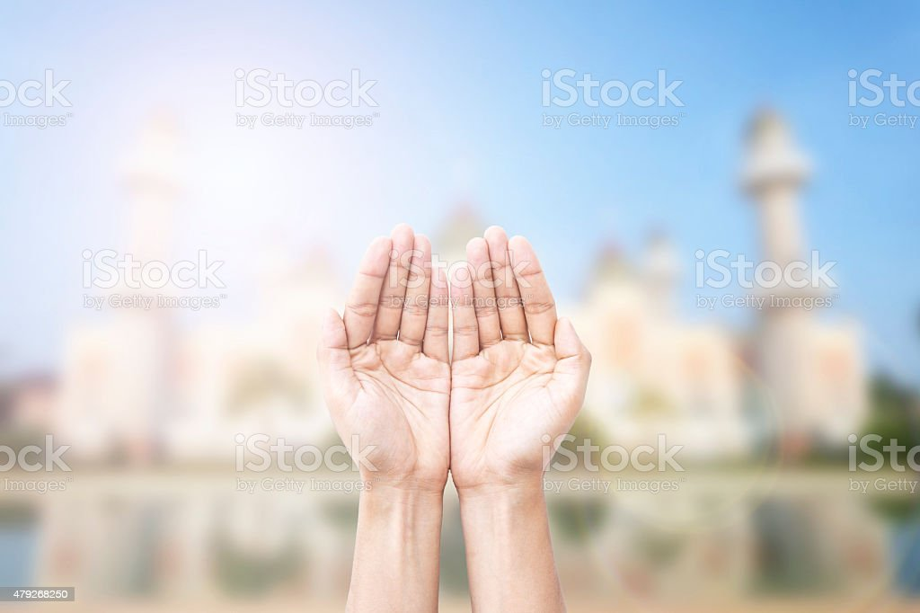 Human hands pray and mosque background. stock photo