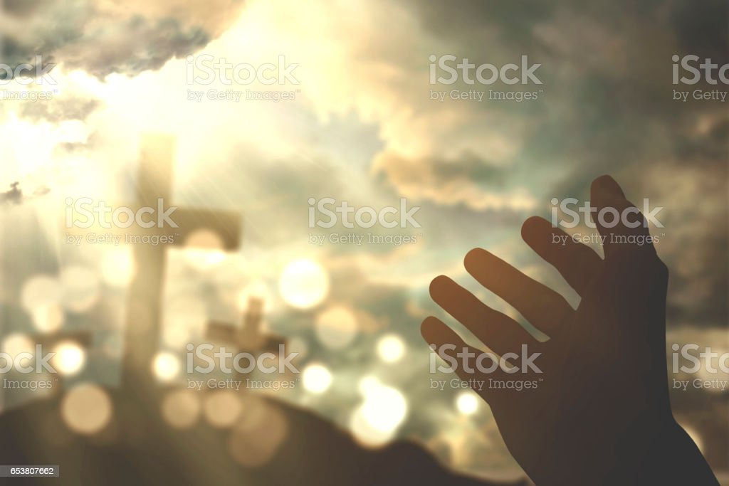 Human hands praying with cross symbol stock photo