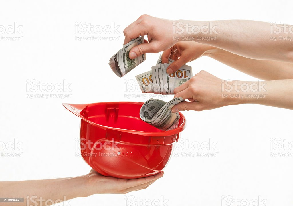 Human hands putting dollars in a red hard hat stock photo