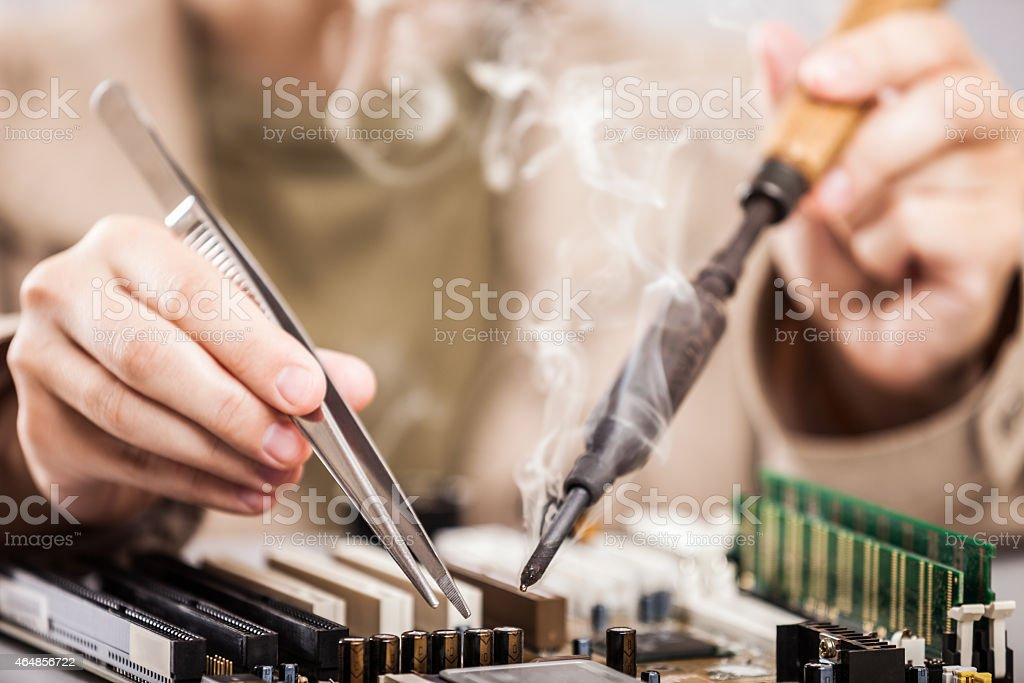 Human hands repairing computer circuit with a soldering iron stock photo