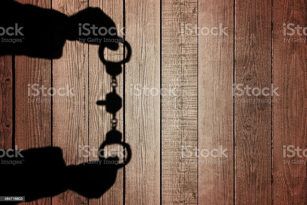 Human Hands Shadow with Handcuffs on Natural Wooden Backround, X stock photo